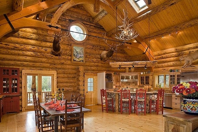An open layout with the view of the kitchen and dining room. The area is decorated with framed artwork and head antlers fixed on the log wall.