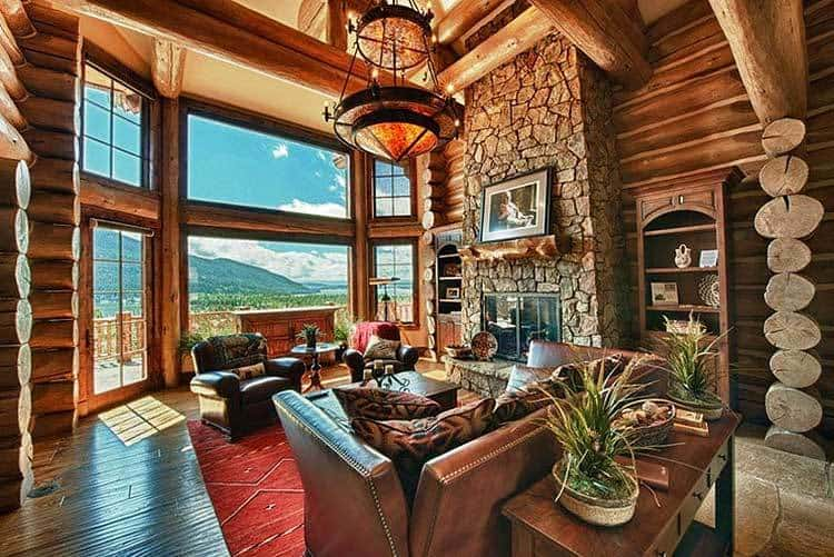 The living room has a stone fireplace and cozy leather seats over a red area rug. It includes full height-glazing that provides a spectacular view of the mountain.