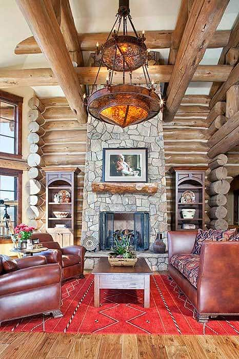 A closer look at the living room shows the marvelous accent wall and a two-tier chandelier hanging from the soaring ceiling styled with log beams.