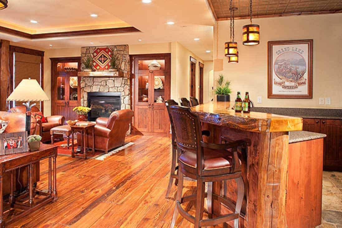 An open floor plan layout with a view of the family room and wet bar. Hardwood flooring and ambient lighting create a cozy atmosphere.