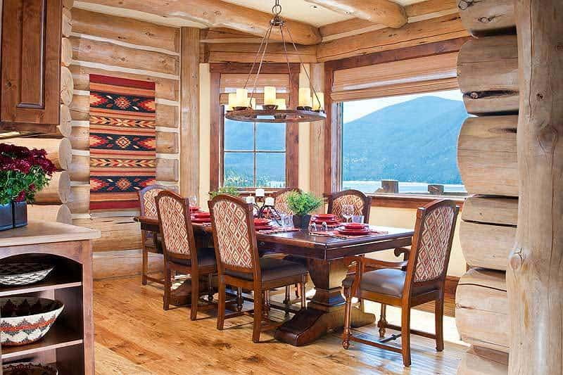 The dining area has a dark wood dining set illuminated by a round chandelier. There are also framed windows that bring natural light in.