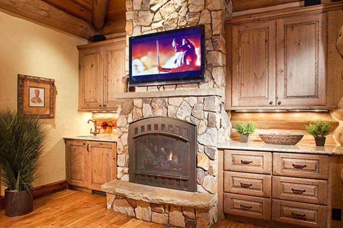 The stone pillar that holds the TV and fireplace is flanked by built-in cabinets.