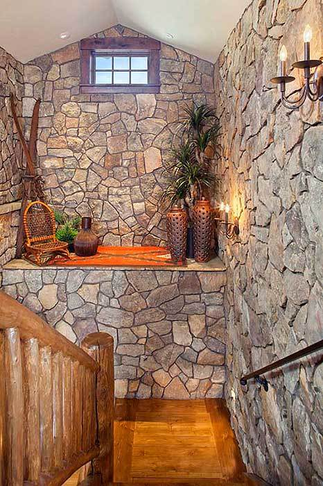 A fabulous nook on the landing decorated with perforated vases and candle sconces mounted on the stone walls.