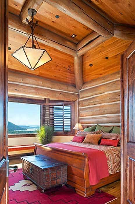 The bedroom with a geometric dome pendant and a cozy bed complemented by a dark wood trunk chest.