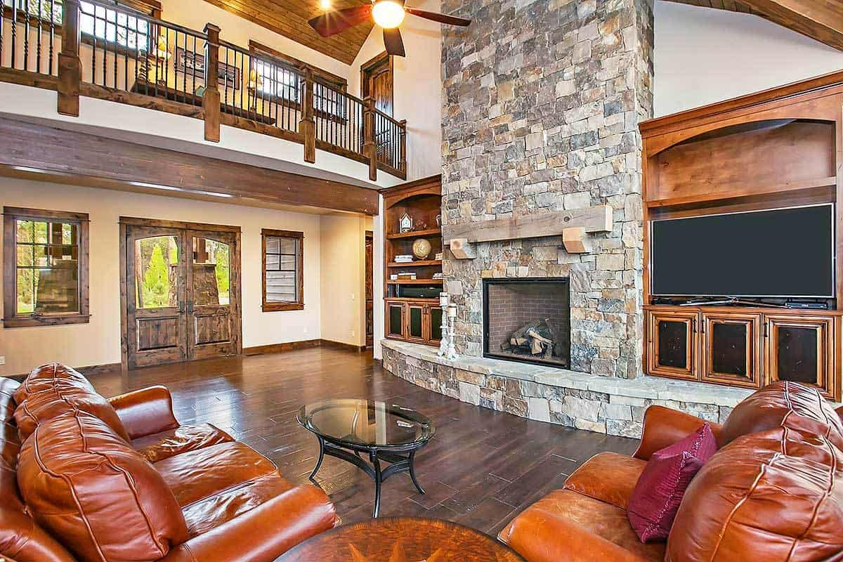 The living room with a high cathedral ceiling and brown leather seats facing the stone brick fireplace.