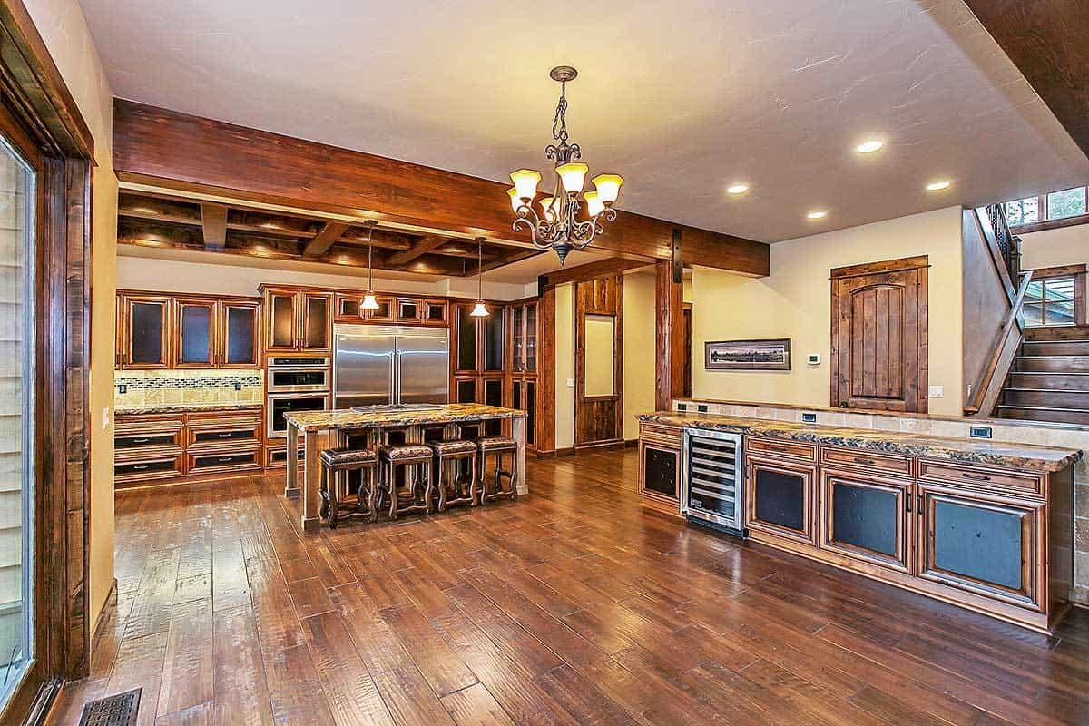 The spacious kitchen boasts granite countertops and a classic chandelier that provides ambient lighting.