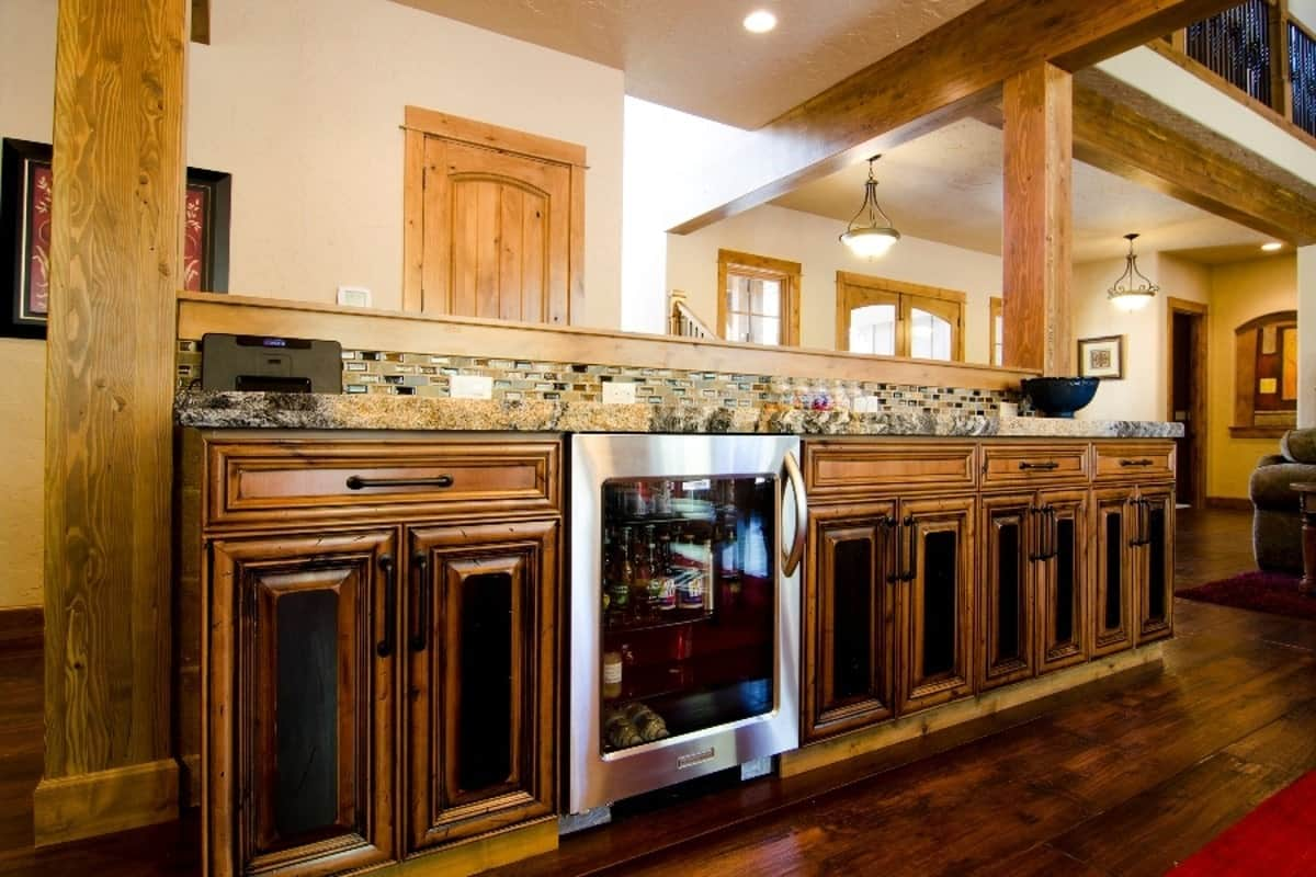 A built-in buffet guarded by wooden columns. It has a beverage fridge and custom cabinets that blend in with the hardwood flooring.