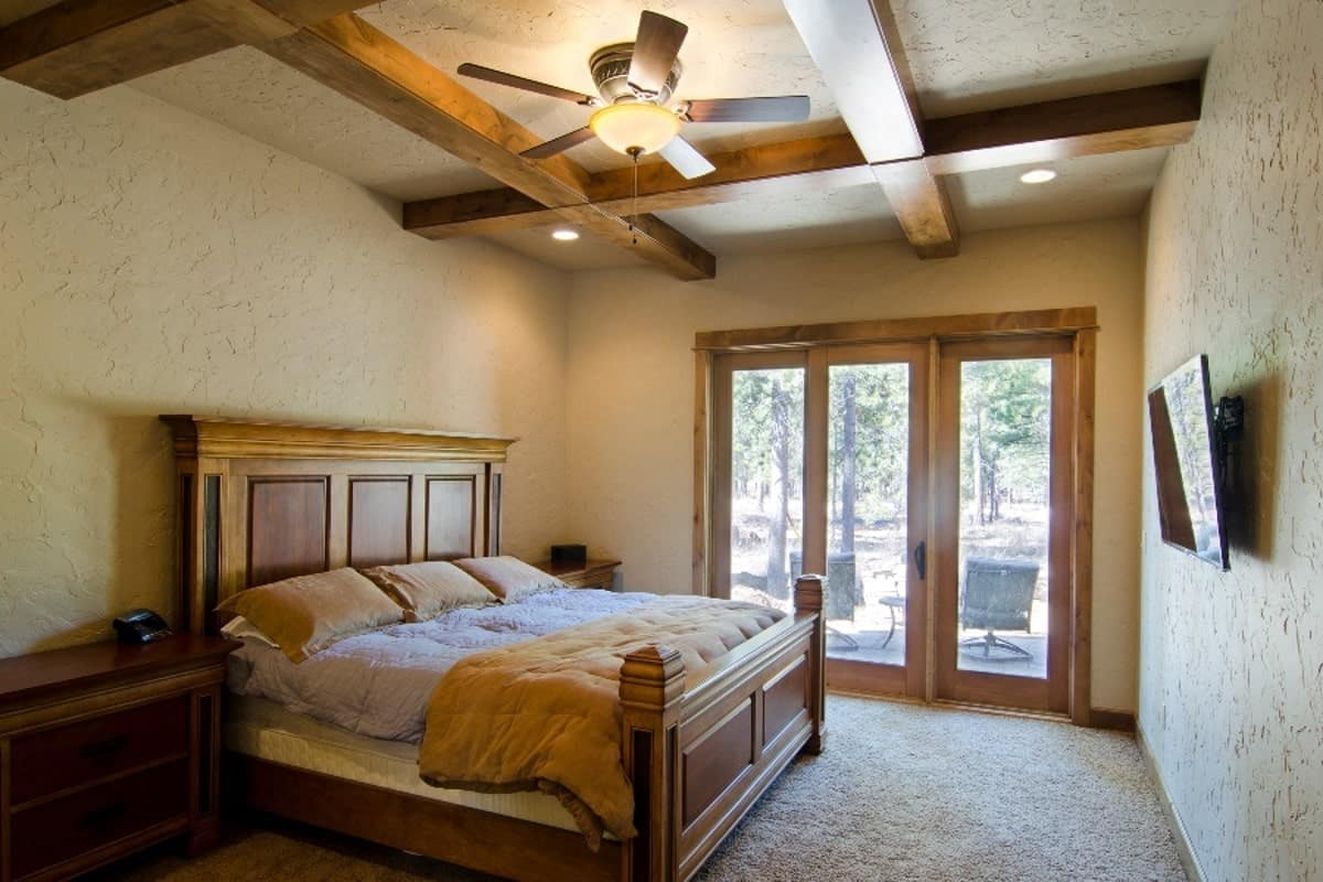 The primary bedroom showcases a beautiful coffered ceiling and textured walls mounted with a TV. Sliding glass doors on the side lead to the open terrace.