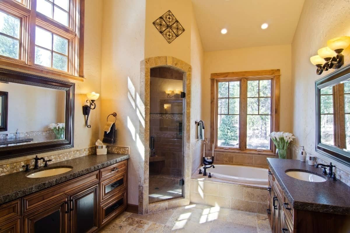 The bathroom is loaded with facing vanities, a deep soaking tub and a walk-in shower enclosed in an arched glass door.