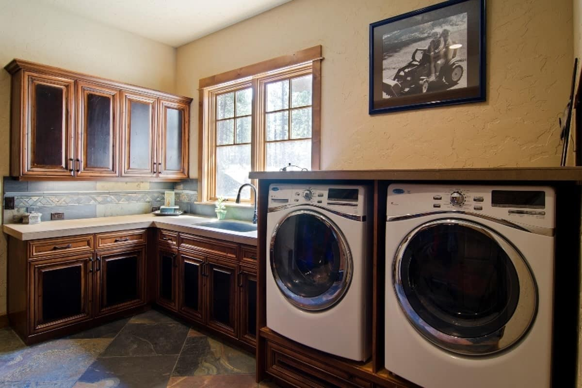 The laundry room is equipped with a washing machine, a dryer and an undermount sink. It has tiled flooring and beige textured walls adorned by a framed photo.