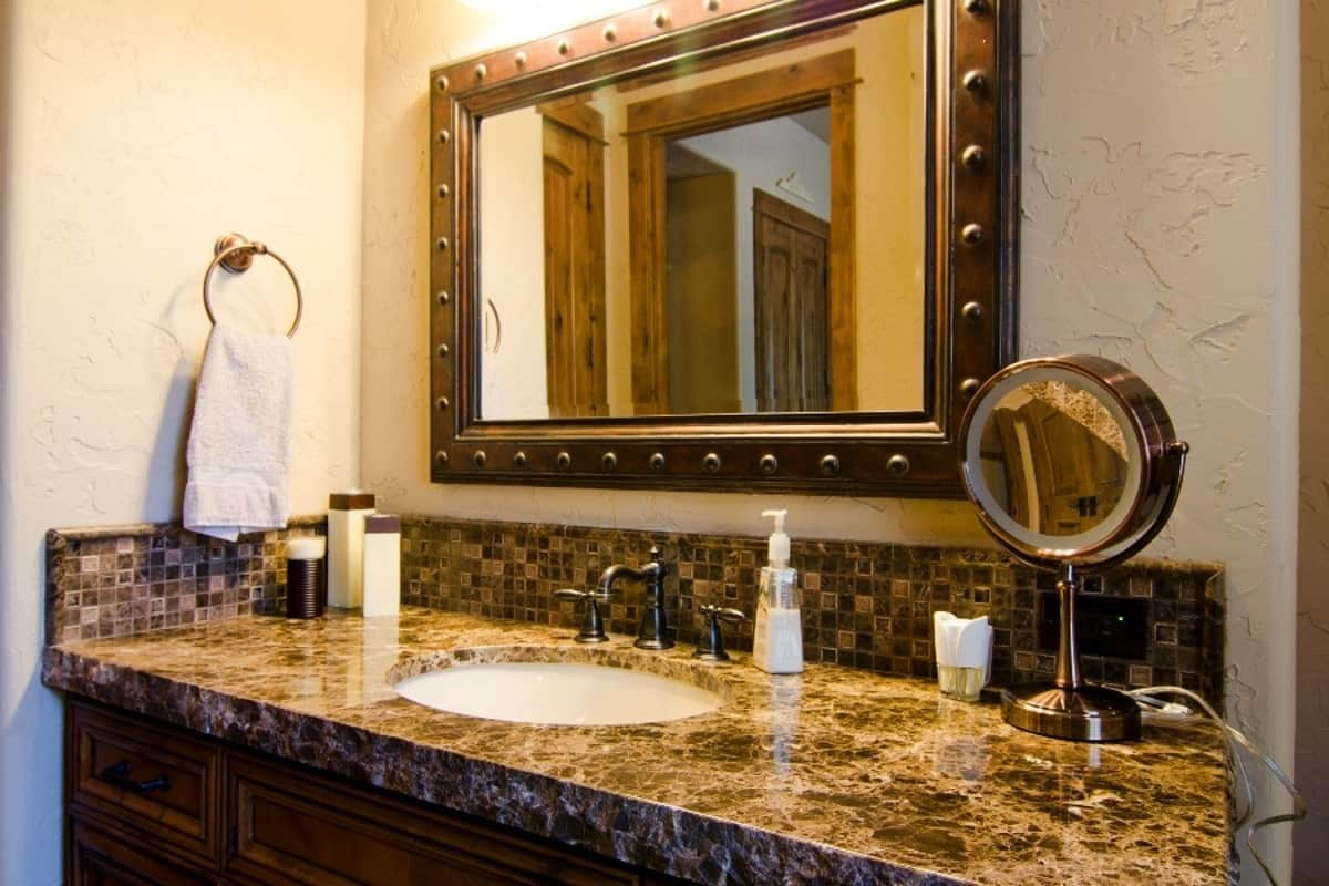 A closer look at the vanity shows an elegant granite countertop and an undermount sink. It is paired with a large framed mirror hanging above the mosaic tile backsplash.