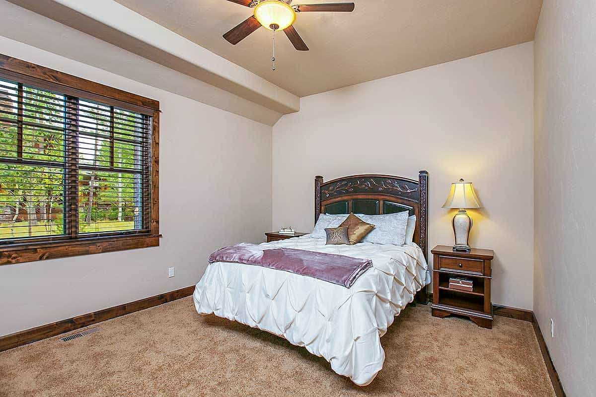 This bedroom has an ornate bed flanked by wooden nightstands. It is illuminated by a classic table lamp and a flush light integrated to a fan.