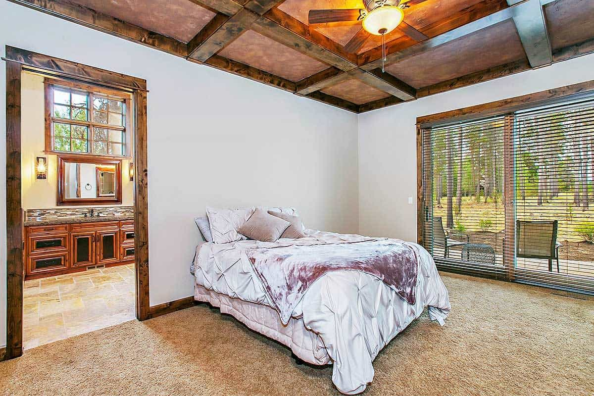 An en suite with beige carpet flooring and a rustic coffered ceiling mounted with a fan. It includes a cozy bed and large windows covered in roller blinds.