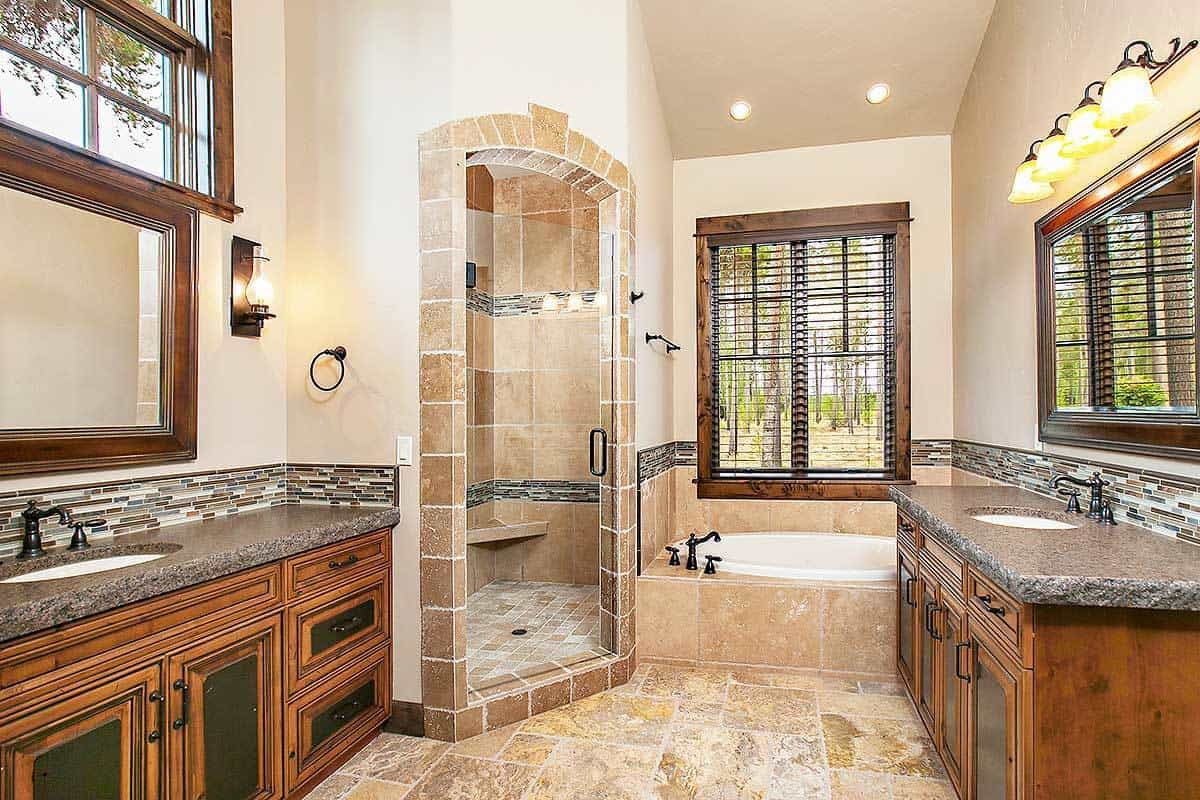 This bathroom has a similar layout with the first bathroom. Both have facing vanities, a drop-in tub, and a walk-in shower.