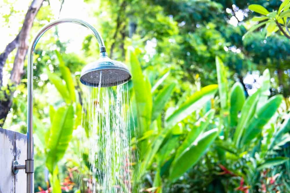 An outdoor shower beside the lush greenery of the garden.