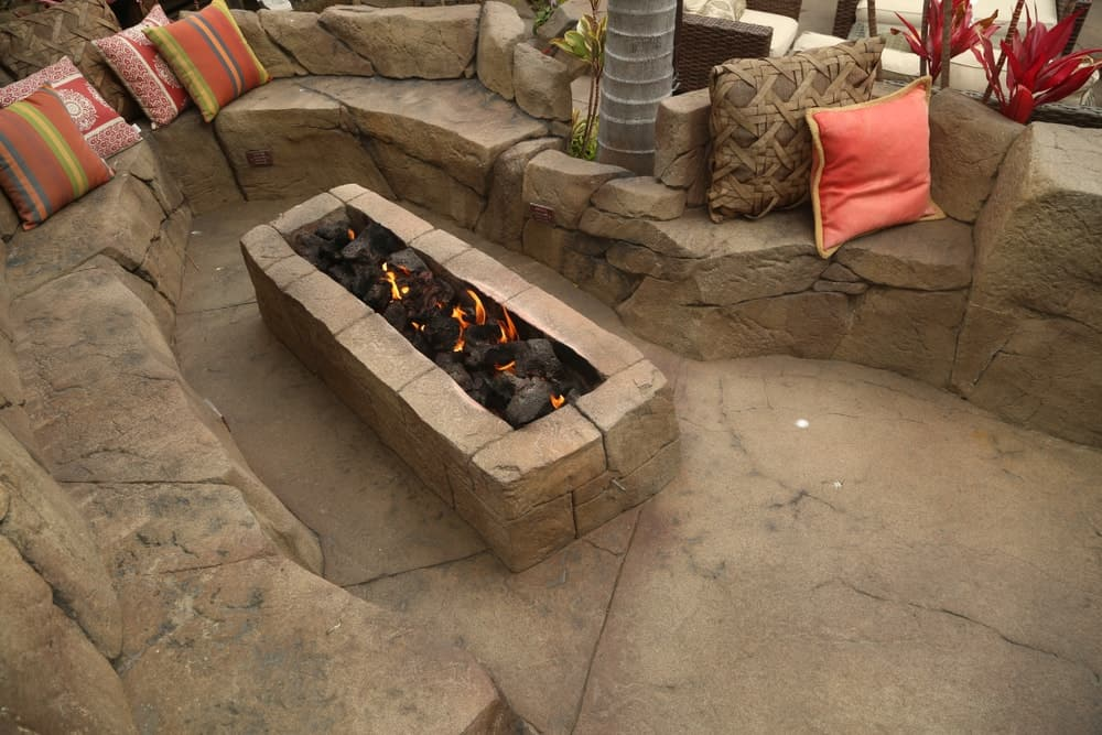 A fancy and luxurious stone firepit with matching stone benches.