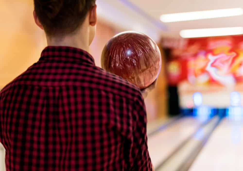 A man about to roll his bowling ball in an indoor bowling alley.