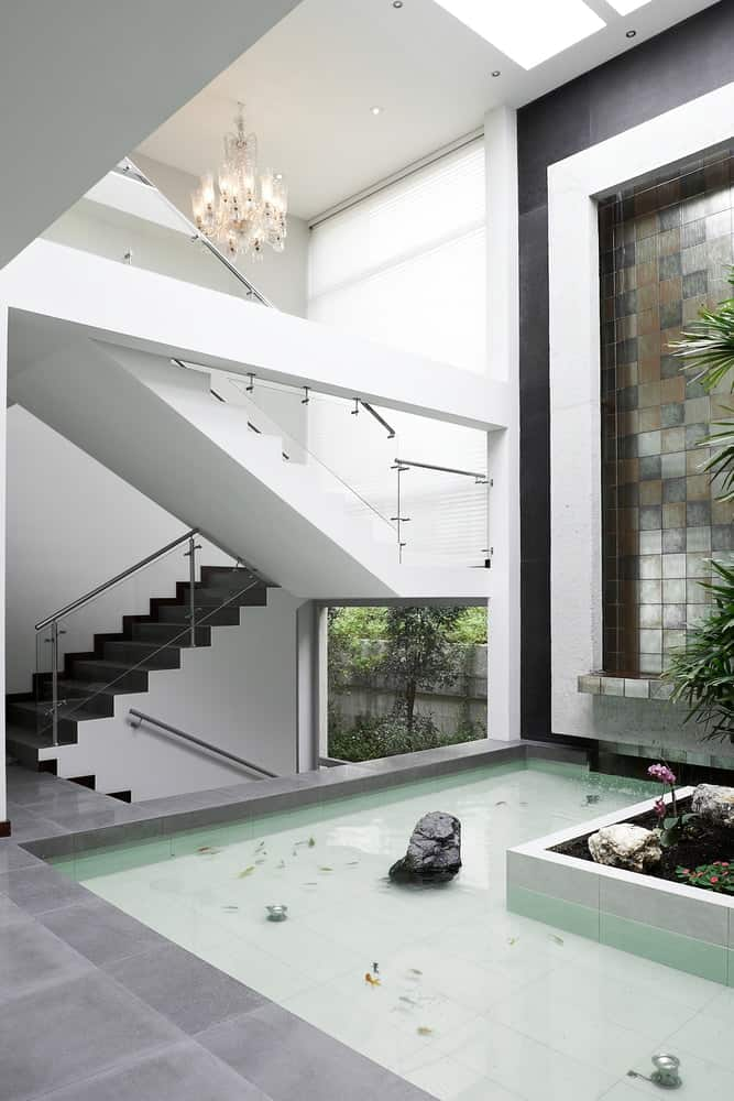 A luxurious indoor waterfall and indoor pond by the stairs.