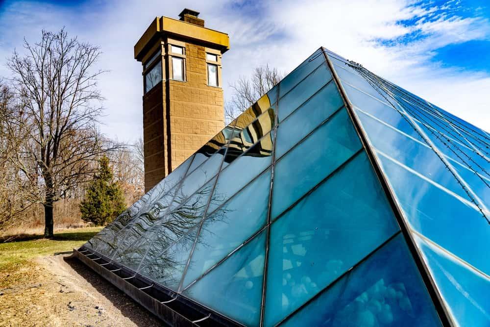 The exterior of a glass pyramid home.