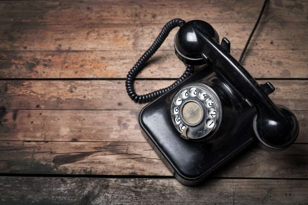 A vintage rotary dial phone on a wooden surface.