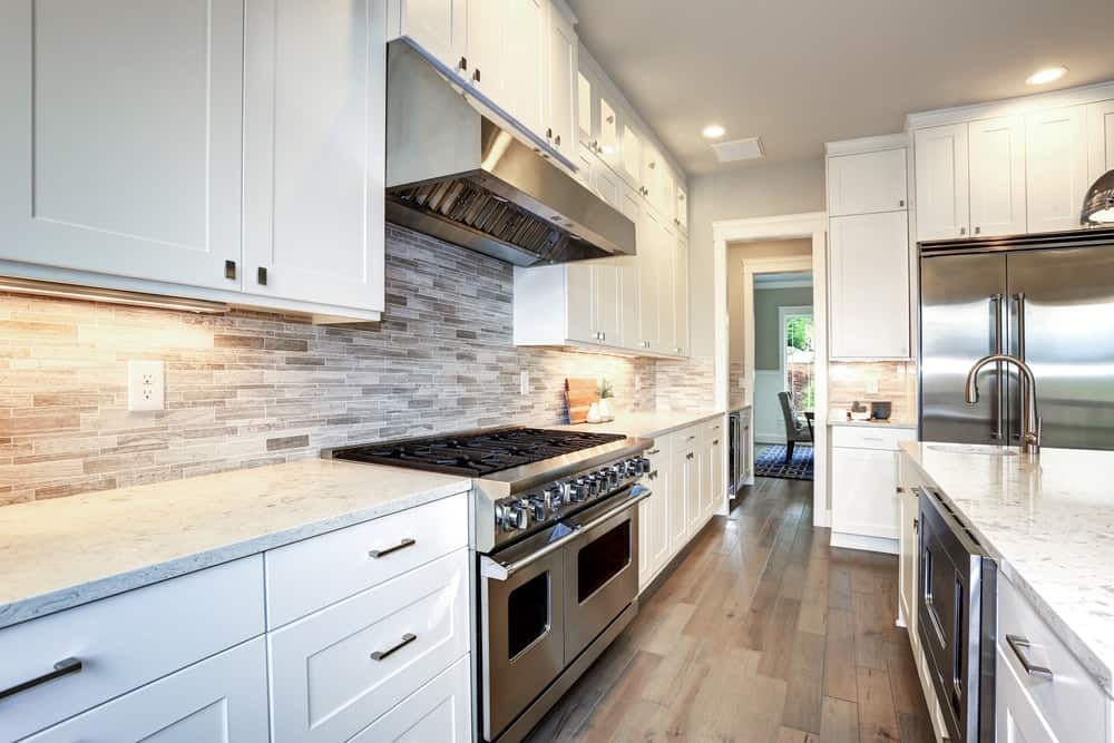 A beautiful kitchen with white shaker cabinets and modern stainless steel appliances.
