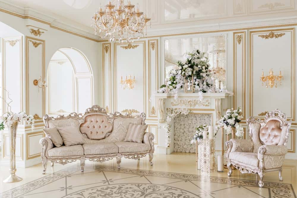 A Victorian-style living room with antique furniture and a luxurious chandelier.