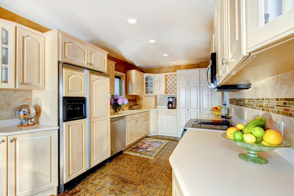 A luxurious kitchen with a fridge that blends in well with the surrounding cabinetry.