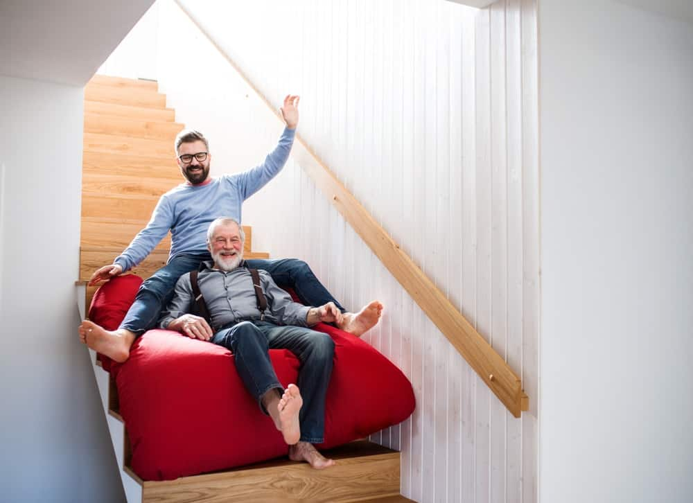 A senior and an adult man sliding down the stairs on a red bean bag.