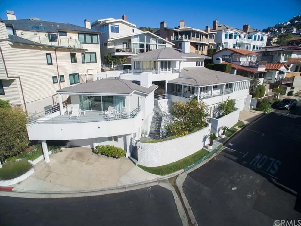 The beautiful beach house has a bright exterior complemented by large windows and balconies to maximize the gorgeous beach scenery. Images courtesy of Toptenrealestatedeals.com.