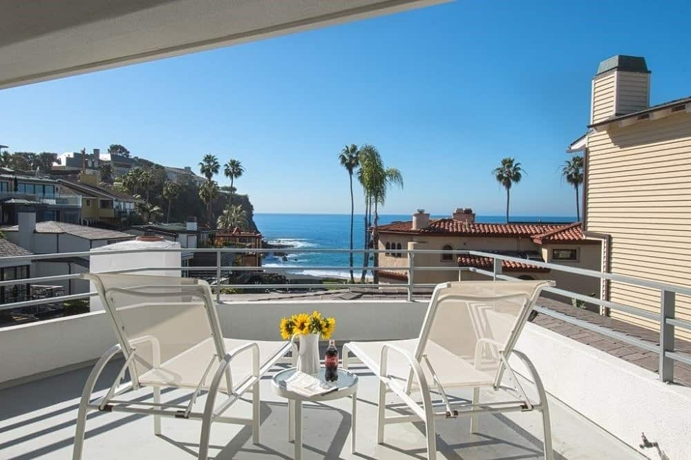One of the balconies have a couple of lawn chairs to better enjoy the beautiful beach scenery in the distance. Images courtesy of Toptenrealestatedeals.com.