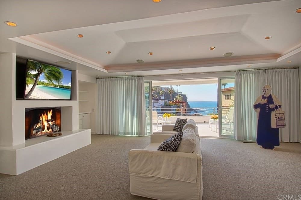 This spacious and airy carpeted living room has a large beige sofa facing a white fireplace with a wall-mounted TV above it. These are all topped with a beautiful white cove ceiling. Images courtesy of Toptenrealestatedeals.com.
