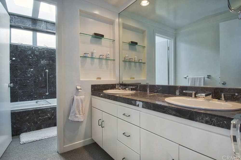 This simple primary bedroom has a large two-sink vanity with a contrasting black countertop paired with a wide wall-mounted mirror. Beside this is the entrance to the walk-in shower area. Images courtesy of Toptenrealestatedeals.com.