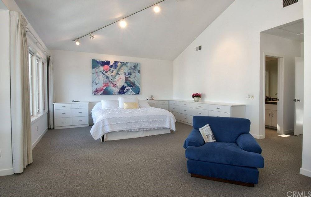 This is a spacious and airy primary bedroom with a large white bed adorned with a large colorful modern artwork mounted on the white wall above it. There is also a blue cushioned arm chair for a relaxing reading nook. Images courtesy of Toptenrealestatedeals.com.