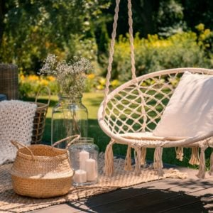 A rope swing with a pillow on a patio with wicker baskets, a rug and a blanket on a wooden deck in the garden.