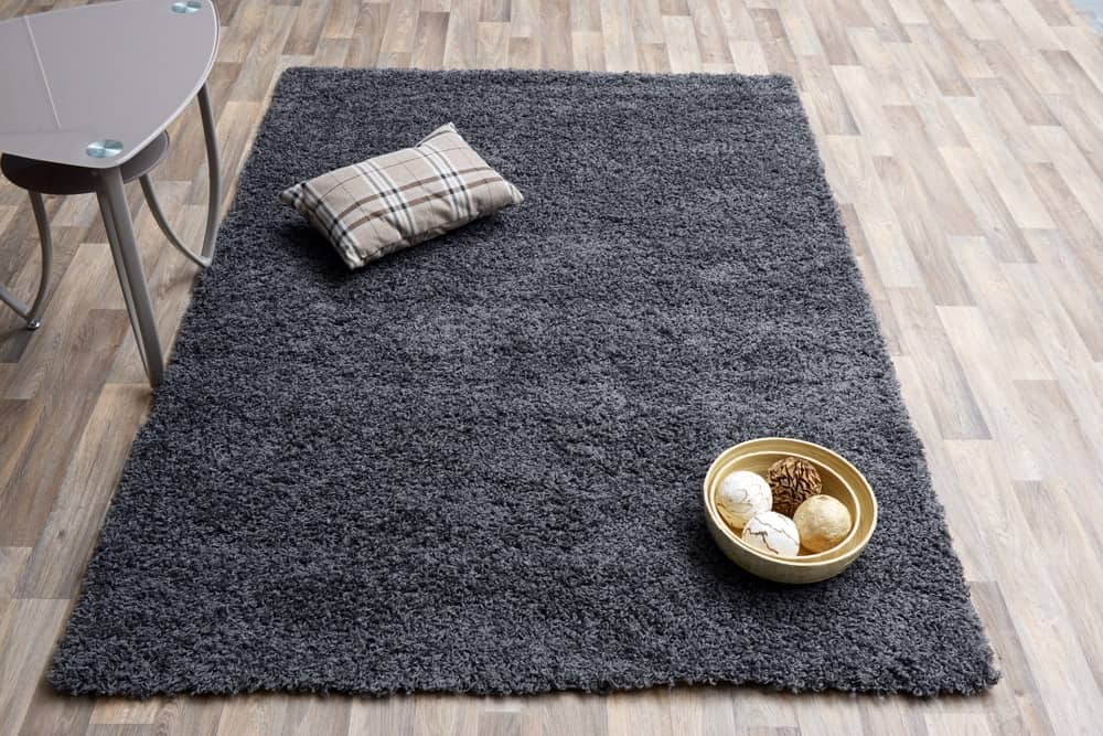 A charcoal gray rug on a light hardwood flooring.