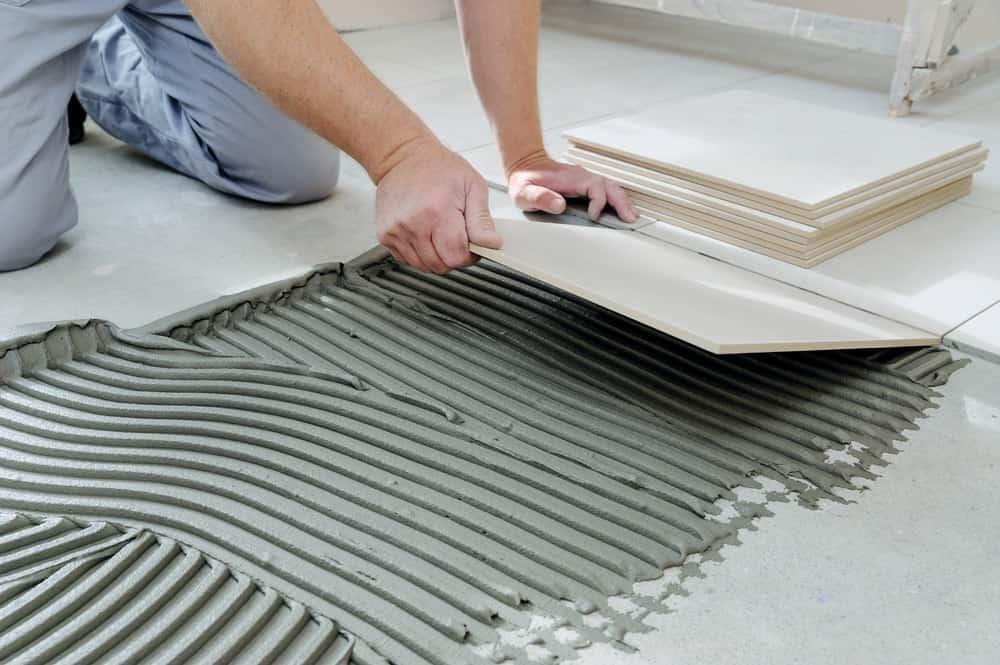 A man installing white tiles onto the floor.