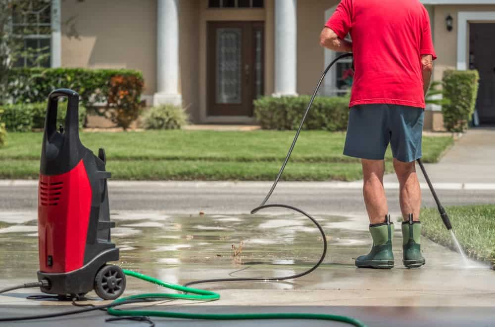 A man cleaning the driveway with a high pressure hose.