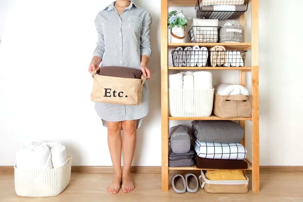 A woman and her tidy wooden shelf storage.