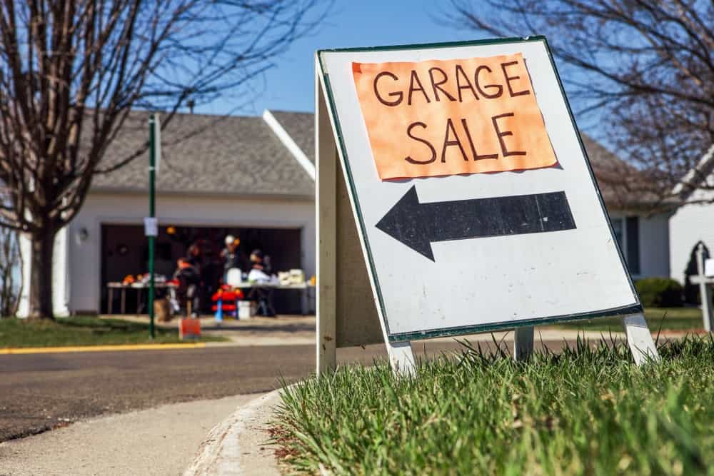 A wooden garage sale sign on a grass lawn.