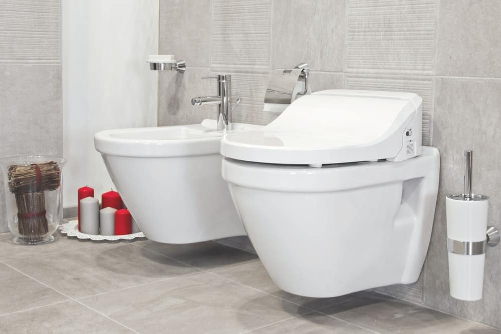 A modern floating toilet in a bathroom with gray tiles.