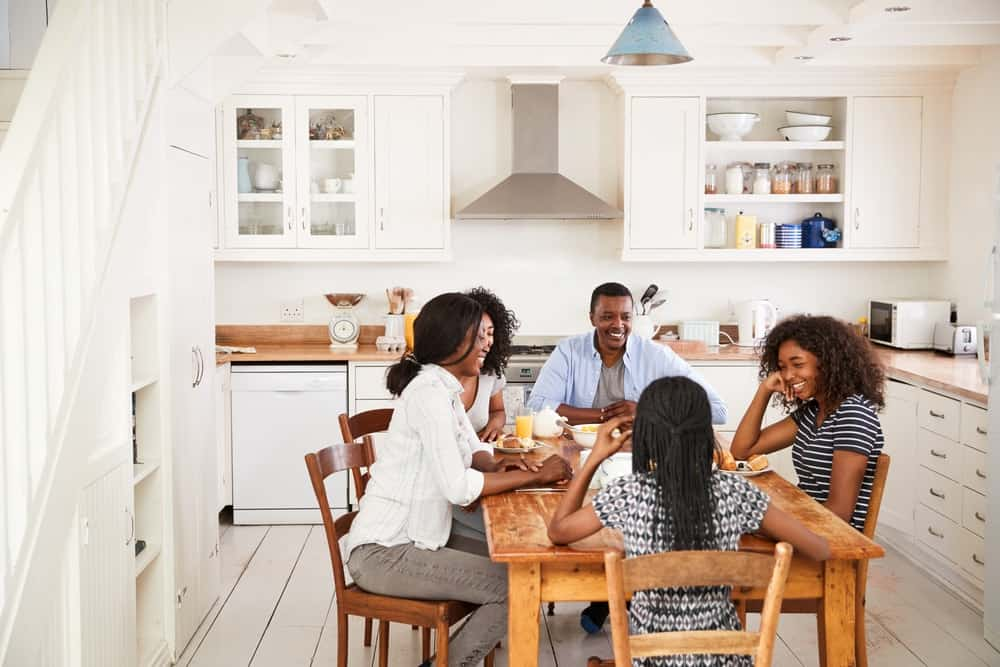 A family enjoying breakfast in the kitchen around a wooden dining table.
