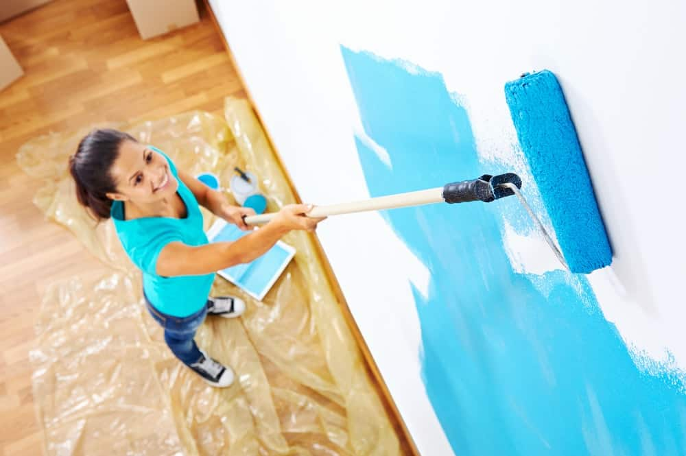 A woman painting the white wall with blue paint using a roller.