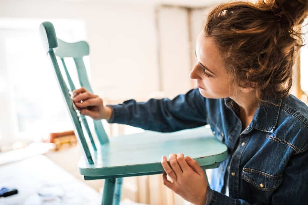 A woman distressing a wooden chair.