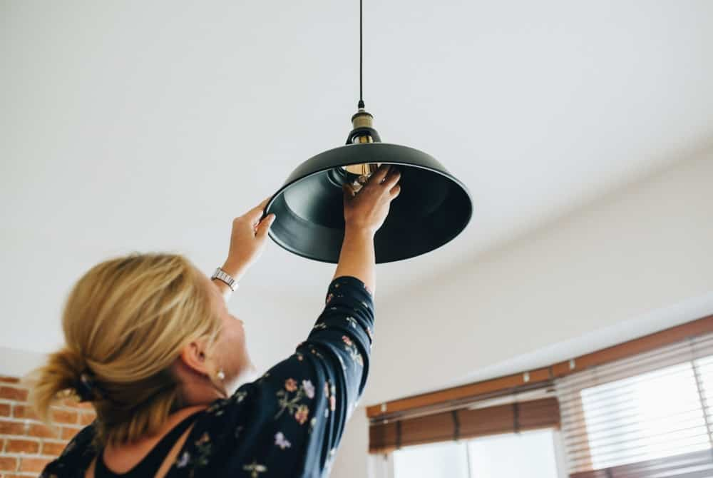 A woman changing the light bulb of a pendant light.