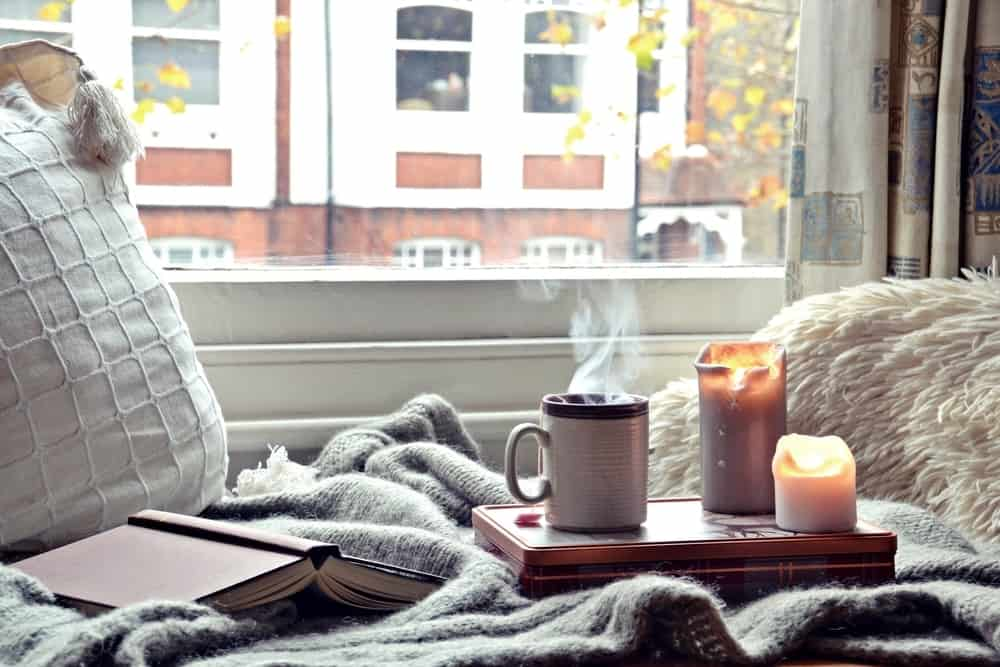 Close-up of a reading nook by the window with a cup of coffee and scented candles.