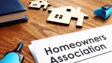 Home Owner's Association documents on a desk with house models.