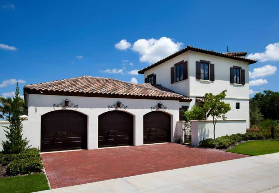 A closer look at the garage exteriors of the home flaunts of the three arched garage doors that matches the house perfectly with its dark brown tone topped with intricate wall lamps above each one.
