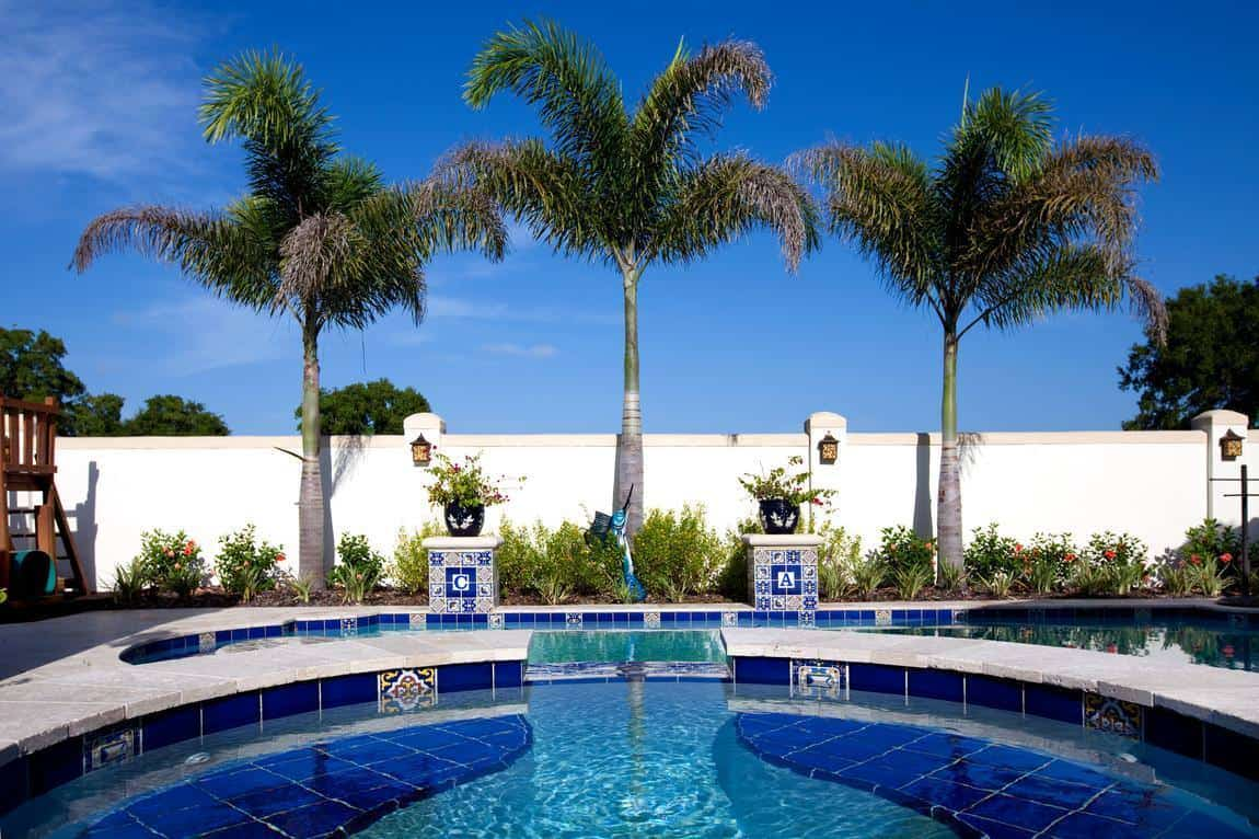 This is the view from the jacuzzi-type pool. You can see here that there is a large pool next to it bordered with tall tropical trees and shrubbery to complement the concrete walls surrounding the backyard.