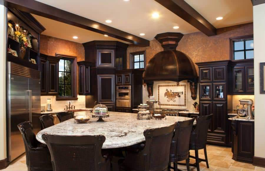 This homey kitchen has beige walls complemented by the dark brown tone of the exposed wooden beams of the ceiling that matches with the cabinetry, vent hood and the chairs surrounding the large breakfast bar of the kitchen island.