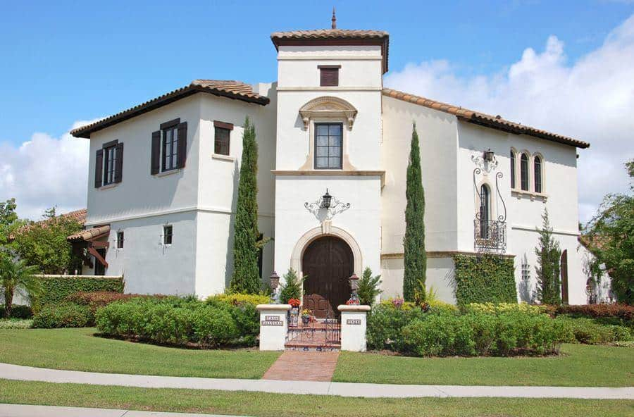 A large white 2-Story Mediterranean-style house with gorgeous earthy roofs that matches well with the wooden window shutters and arched main door. These are then complemented by the lush greenery of the surrounding landscaping.
